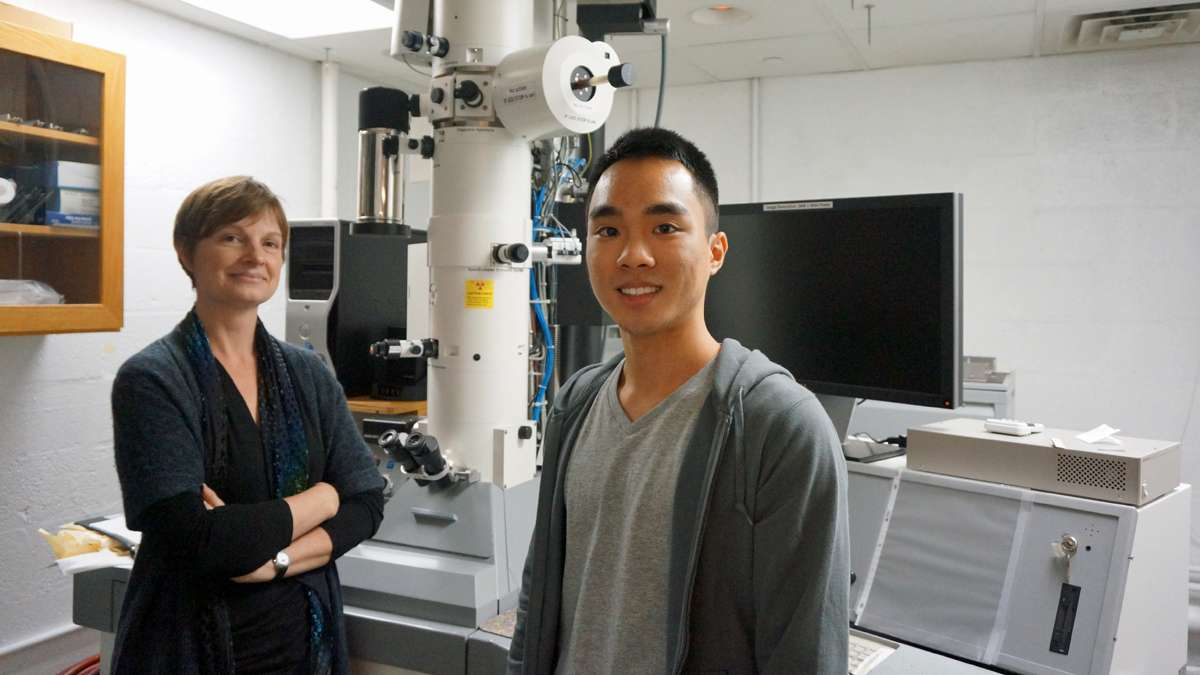Princeton neuroscientist Lisa Boulanger (left) and undergraduate Joseph Park (right) stand beside the electron microscope that enabled them to count synapses in the mouse hippocampus. (Jessica McDonald/WHYY)